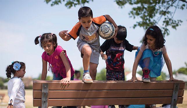 Des enfants réfugiés syriens s'amusent sur un banc de parc. Ils participaient, en juillet dernier à Toronto, à un camp de jour destiné à les aider à s'intégrer à l'école en septembre. Photo de The Canadian Press/Chris Young.